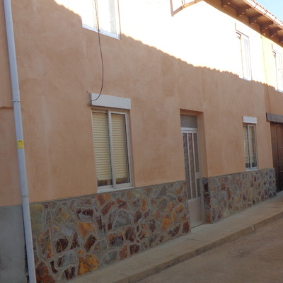 Revoque de fachada con cemento coloreado y piedra natural en Leon