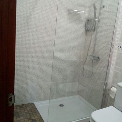 Plato de ducha con grifería y mampara de cristal.