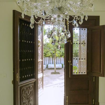 Puerta de madera con ventanas y rejas de forja con detalles dorados