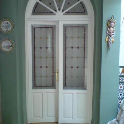 Puerta doble vidriera con medio punto.