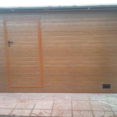 Puerta seccional panel gofrado imitación madera y peatonal inscrita