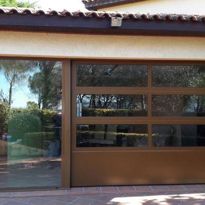 Puerta seccional con perfileria de aluminio y fijo adosado, con relleno de vidrio doble