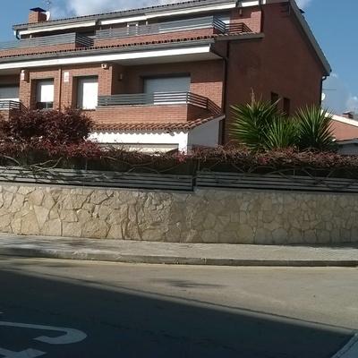 Colocación de piedra natural en un  muro perimetral cara exterior del frente de casa adosada en Barcelona