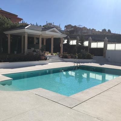 Vista de piscina con porche al fondo