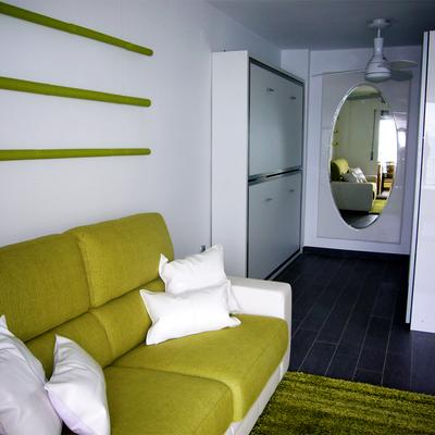 Zona del sofá en primer plano. Literas y zona vestidor al fondo