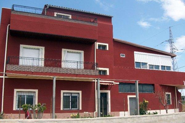 Foto fachada en monocapa raspado color rojo de estucados for Zocalos de fachadas fotos