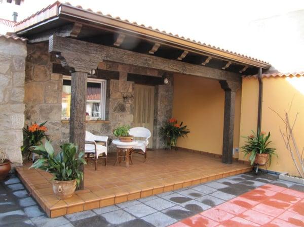 Foto porche r stico con paredes con piedra natural de for Amaru en la puerta de un jardin