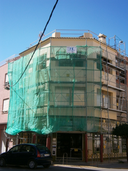 revstimiento de fachada y montaje de andamio con protección para comercio en planta baja