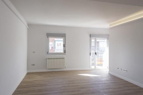 Salón moderno con iluminación LED en el techo, abierto a la cocina y con balcón