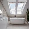 Baño con techo abuhardillado y bañera exenta
