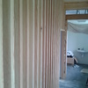 Celosía estructural de madera, tamizando la vista del acceso a los aseos