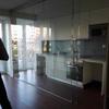 Cocina integrada en salón con mampara de vidrio