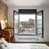Dormitorio con grandes ventanales al ático