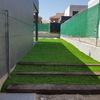 Pasillo de acceso a terraza-piscina con cesped artificial