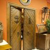 Puerta rústica de dos hojas con duelas en forma de espiga, mirilla, postigo y reja.