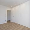 Dormitorio de estilo moderno con armario empotrado e iluminación LED en el techo