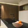 Revestimiento practicable del volumen del baño de cortesía y detalle de isla de cocina