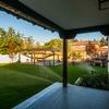 Vista del porche desde la casa, con suelo de tarima exterior y toldo corredero