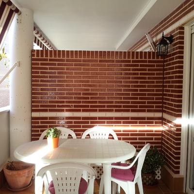 Instalar cristal separador entre terrazas sobre muro de for Muro de separacion terraza