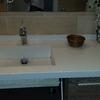 Lavamanos de silestone sobre mueble y pulido suelo terrazo