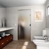 Puerta cristal templado abatible en el lavabo.