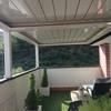 Instalación de toldos verticales de plástico transparente en pérgola de terraza