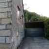 Revocar fachada lateral y alero bajo teja de una casa de piedra con mortero hidrófugo blanco.